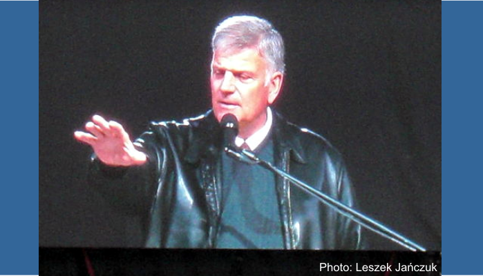 Franklin Graham shown at a podium speaking at a festival in Poland.